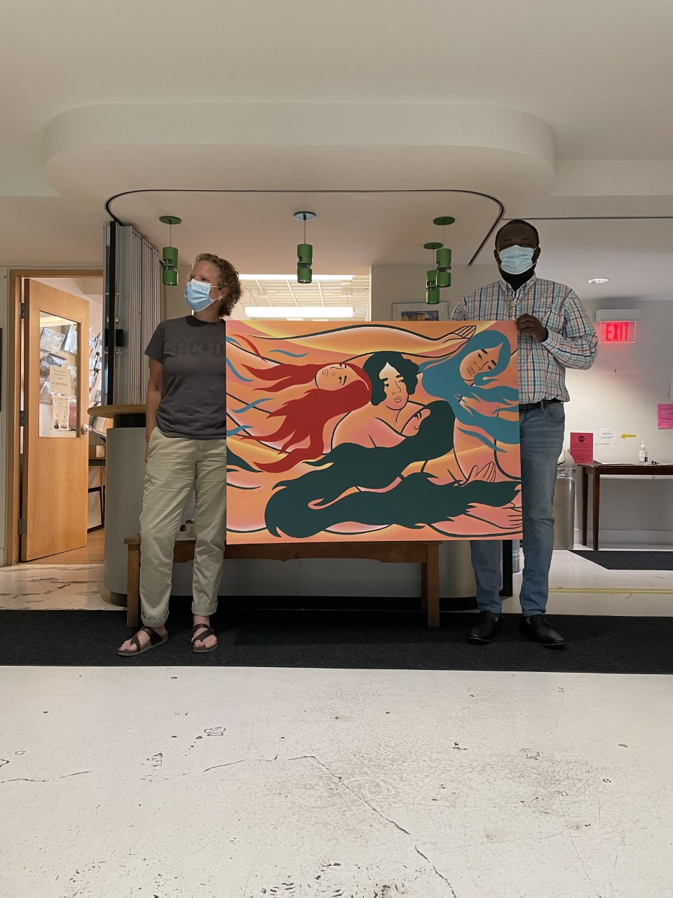 2 PEOPLE STANDING IN OHOTO HOLDING AN ART PIECE